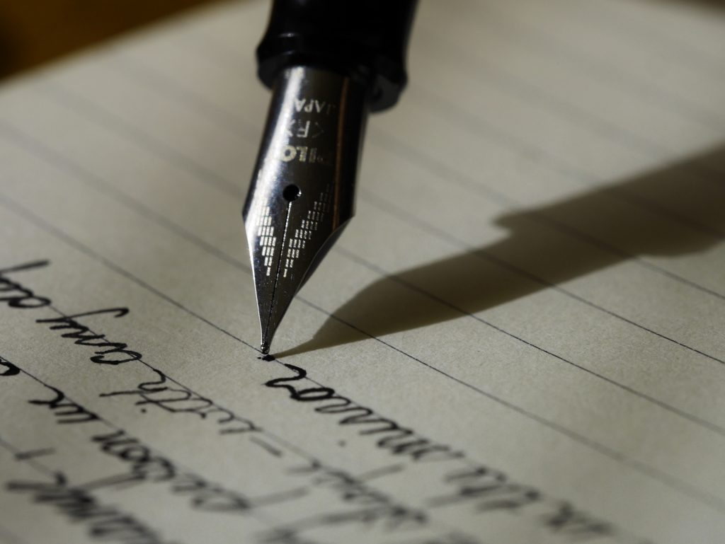 nip of a pen and words written on a page along with the shadow of the pen.