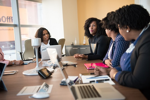 five woman at the conference room discussing steps in preparing presentations