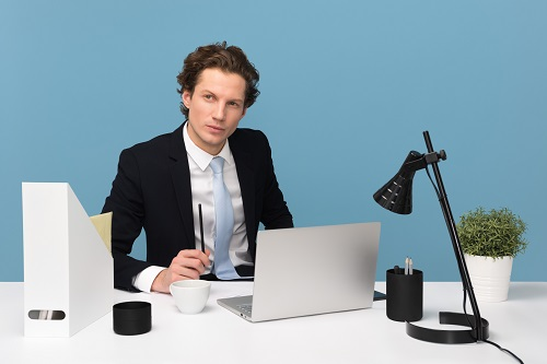 man sitting with laptop computer on desk and lamp to know which jobs require interpersonal skills
