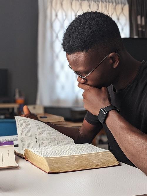man wearing black crew neck shirt reading book for improving reading skills