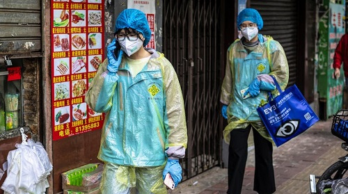 two doctors in blue walking in front of a shop after the coronavirus impact on world economy