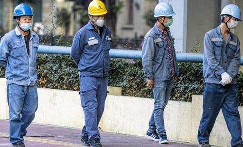 four men in blue walking after controlling coronavirus impact on world economy