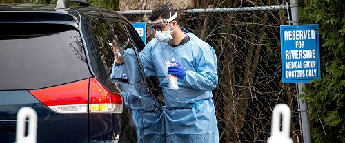 a man in blue beside a black care for treatment of coronavirus