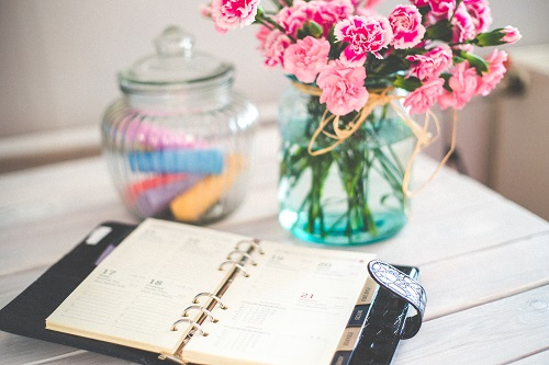 pink flowers and a diary displaying basic organizational plan