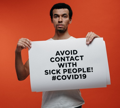 a man holding banner showing safety measures against coronavirus