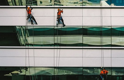 workers going up the building on ropes showing workplace safety hazards