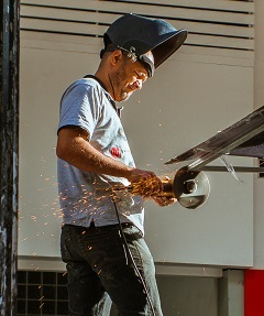 worker cutting iron for workplace safety hazards