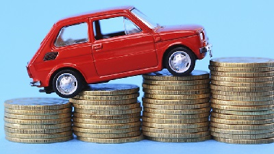 a red car climbing on coins to show How to save money on car insurance