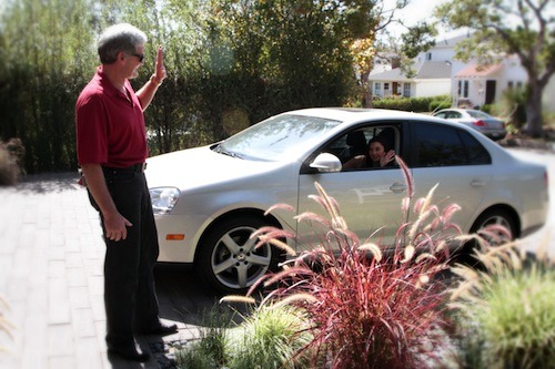 man waving to a woman in the car showing 8 things to know about auto insurance