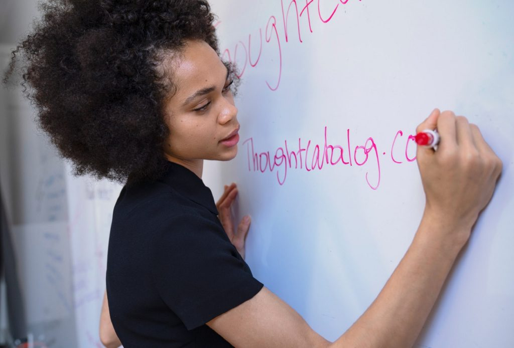 girl writing on white board Education-Trends-2020-to-2021