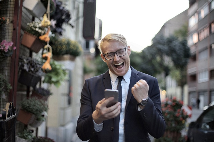 a man in black with a cell phone in hand celebrating a good news message