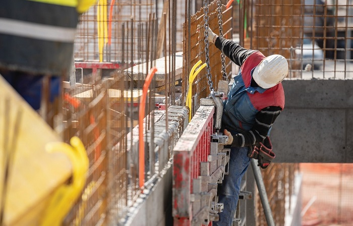 a man iin red coat and white cap showing canadian construction trends